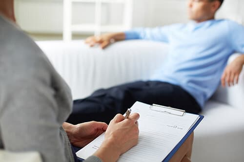 Female psychologist making notes during psychological therapy se
