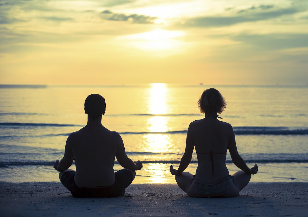 Young couple practicing yoga in the lotus position on the ocean beach during sunset. Cross-process p